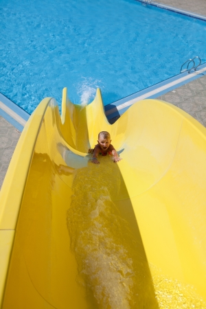 pretty little girl goes down on slide photo