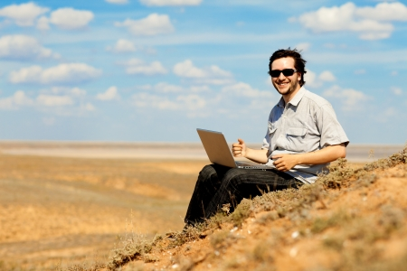 happy man with laptop on the hill photo
