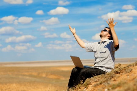 man with laptop praying to the God outdoors Standard-Bild