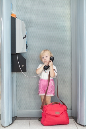 phone number: child with bag talking the phone in the airport Stock Photo