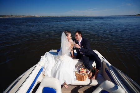 happy young couple having picnic on the yacht photo