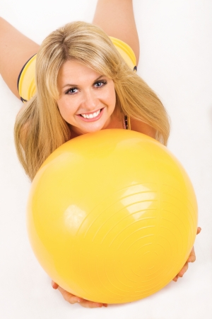 happy girl with fitness ball on the floor photo
