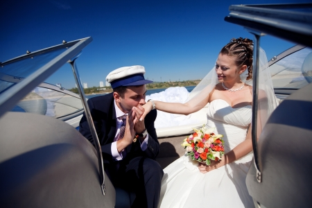 ship captain: captain kissing hand to a lady on the yacht