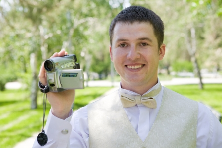 happy groom with videocamera photo