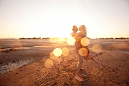 novios besandose: Pareja feliz en la playa Foto de archivo