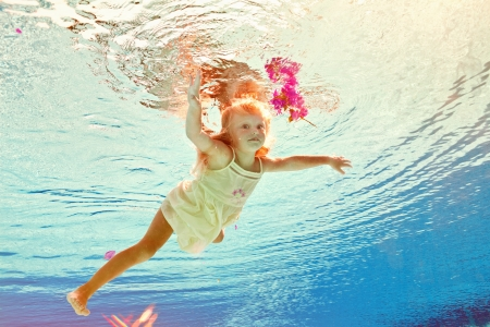 girl in the swimming-pool under water with a flower photo