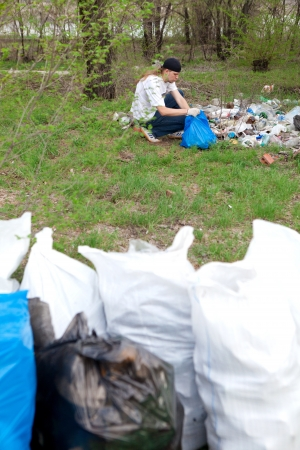 man collecting rubbish in the forest photo