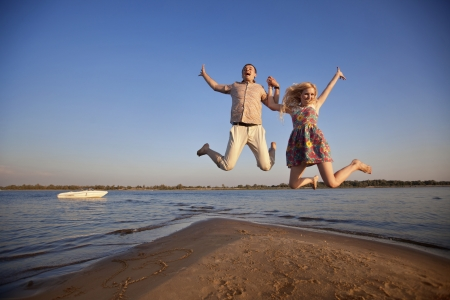 happy couple jumping on the beach photo