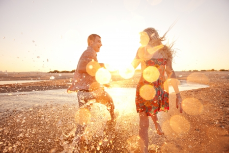 feelings of happiness: happy couple running on the beach Stock Photo