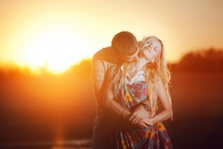 enamorados besandose: feliz pareja bes�ndose en la playa Foto de archivo