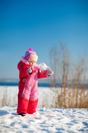 small child throwing snow in winter photo