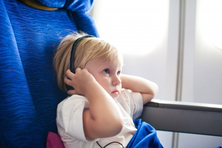 small child with headphones in the plane