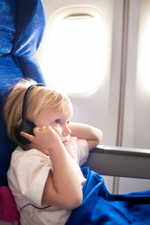 small child with headphones in the plane photo