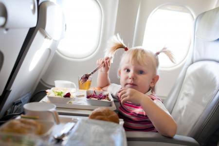 pequeña niña de comer en el avión
