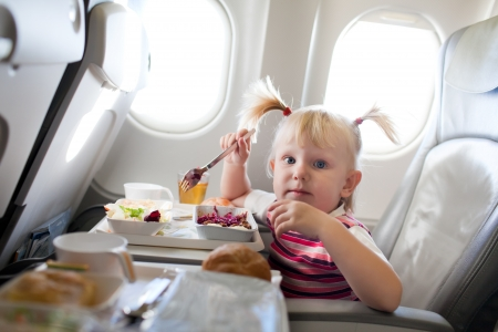 small girl eating in the airplane