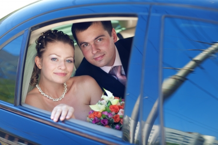 portrait of bride and groom in the car photo