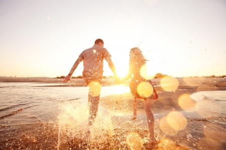 幸せなカップル、ビーチを走る