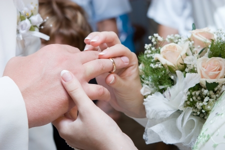 getting together: bride puts on a wedding ring to a groom Stock Photo