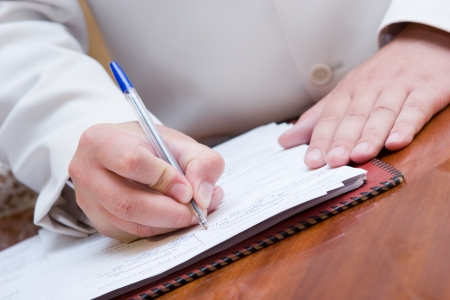 hand with pen: man in suite signing paper