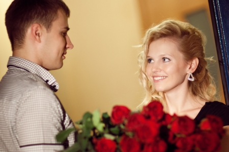 gives: man gives red roses to a girl