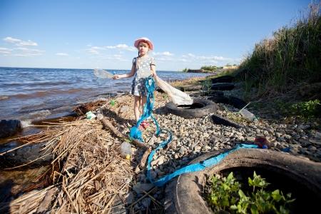 dirty girl: ragazza piccola raccolta dei rifiuti nei pressi del fiume