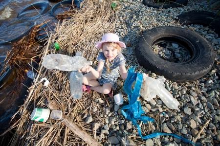 greenpeace: small girl collecting rubbish near the river
