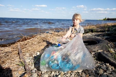 ni�os reciclando: peque�a ni�a recogiendo basura cerca del r�o Foto de archivo