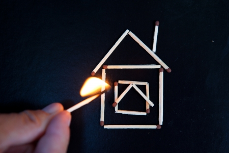 burning house: burning match in hand near the model of the house Stock Photo