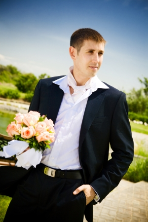 welldressed: well-dressed groom with rose bouquet Stock Photo
