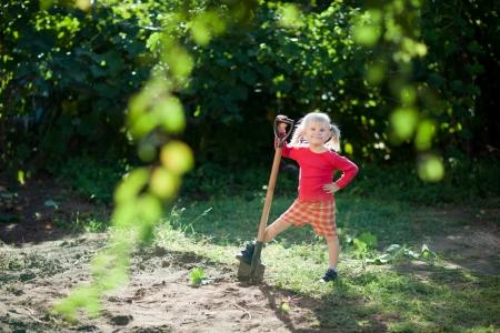 kleine Mädchen hilft zu graben Standard-Bild