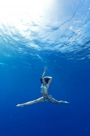 athletic girl making yoga in the sea photo