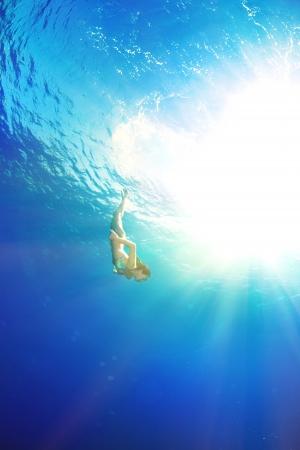 athletic girl diving under the sea 版權商用圖片