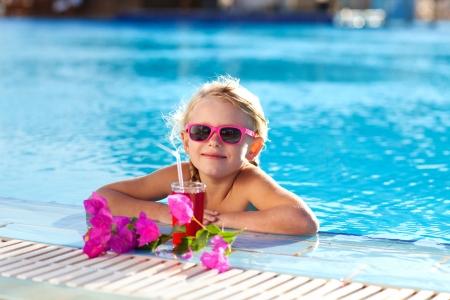klein meisje drinken coctail in het zwembad