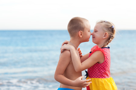 portrait of two children kissing on the beach