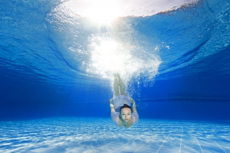 athletic girl diving in the swimming pool photo