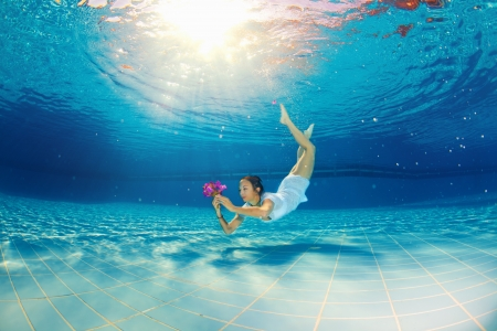 girl diving under the water with flowers