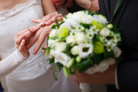bride puts on a wedding ring to a groom photo
