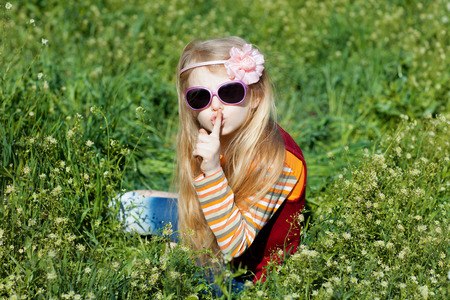 small girl with sunglasses in grass with fingers at lips