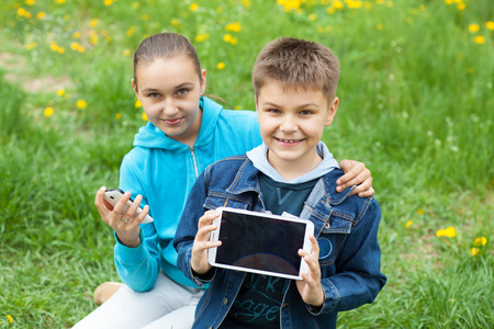 brother and sister with tablet PC and telephone Standard-Bild