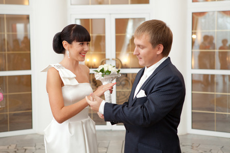 groom putting on a wedding ring to a bride photo