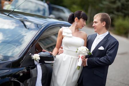 bride and groom near the car