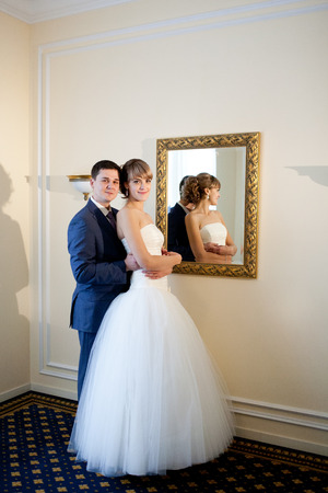 bride and groom by the mirrir
