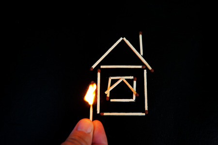 burning match in hand near the model of the house Standard-Bild