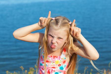 sticking to: girl making face on seashore Stock Photo