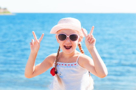 girl showing sign victory with fingers near sea
