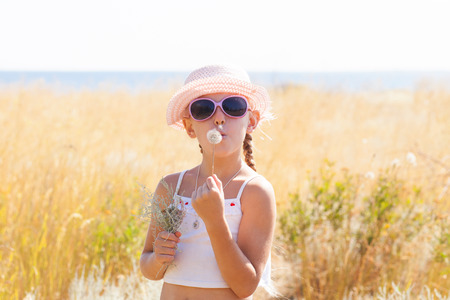 a girl blow on dandelion photo