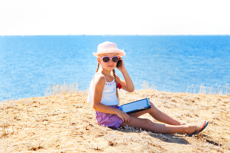 girl on the beach with laptop and phone photo