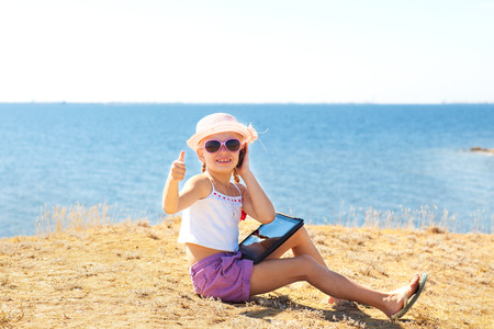 girl on the beach with laptop and phone showing okay Standard-Bild