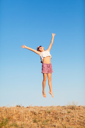 happy small girl jumping outdoors photo