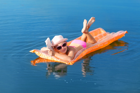 girl on the swimming mattress reading a book photo